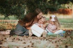 Ευτυχής οικογένεια - mom και δύο κόρες κάθονται σε ένα λιβάδι και διαβάζουν ένα βιβλίο Πικ-νίκ στοκ εικόνα