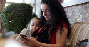 Ευτυχής οικογένεια, mom στηργμένος με την κόρη, το ευτυχείς mom της και την κόρη που χρησιμοποιούν ένα smartphone, καθμένος το αγ φιλμ μικρού μήκους