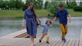 Ευτυχής οικογενειακή έννοια: μητέρα, πατέρας και μικρό παιδί που περπατούν από τον ποταμό, που έχει τη διασκέδαση φιλμ μικρού μήκους