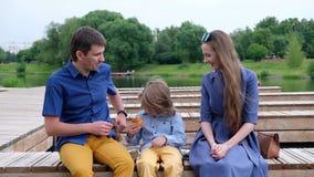 Ευτυχής οικογενειακή έννοια: συνεδρίαση μητέρων, πατέρων και μικρών παιδιών με τον ποταμό και την κατανάλωση croissant απόθεμα βίντεο