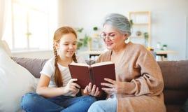 Ευτυχής οικογενειακή γιαγιά που διαβάζει στο βιβλίο εγγονών στο σπίτι στοκ εικόνες με δικαίωμα ελεύθερης χρήσης