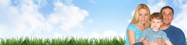 Ευτυχής οικογενειακή επικεφαλίδα με τα σύννεφα και τη χλόη Στοκ φωτογραφία με δικαίωμα ελεύθερης χρήσης