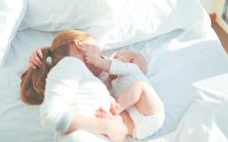 Ευτυχής οικογενειακή μητέρα με το παιχνίδι και το αγκάλιασμα μωρών στο κρεβάτι στοκ εικόνες