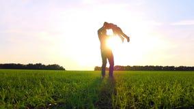 Ευτυχής οικογενειακή παίζοντας φύση στο πάρκο στο ηλιοβασίλεμα Ο πατέρας κρατά το γιο του από τα όπλα και τις στροφές με τον σε έ φιλμ μικρού μήκους