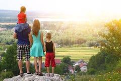 Ευτυχής οικογενειακή στάση που στέκεται σε έναν βράχο στα βουνά Έννοια ο Στοκ Φωτογραφία
