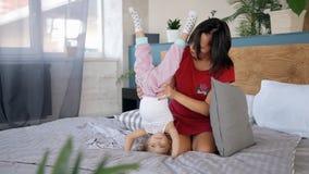 Ευτυχής οικογενειακή στιγμή μεταξύ λίγης κόρης και της νέας μητέρας στην κρεβατοκάμαρα απόθεμα βίντεο