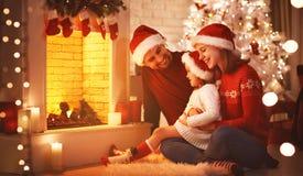 Ευτυχής οικογενειακή συνεδρίαση από την εστία στη Παραμονή Χριστουγέννων στοκ εικόνες