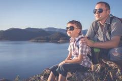 Ευτυχής οικογενειακή συνεδρίαση κοντά σε μια λίμνη στο χρόνο ημέρας Στοκ Φωτογραφίες