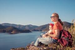 Ευτυχής οικογενειακή συνεδρίαση κοντά σε μια λίμνη στο χρόνο ημέρας Στοκ φωτογραφίες με δικαίωμα ελεύθερης χρήσης