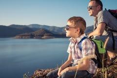 Ευτυχής οικογενειακή συνεδρίαση κοντά σε μια λίμνη στο χρόνο ημέρας Στοκ φωτογραφία με δικαίωμα ελεύθερης χρήσης
