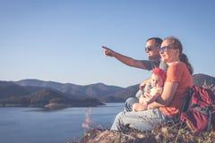 Ευτυχής οικογενειακή συνεδρίαση κοντά στη λίμνη στο χρόνο ημέρας Στοκ φωτογραφίες με δικαίωμα ελεύθερης χρήσης