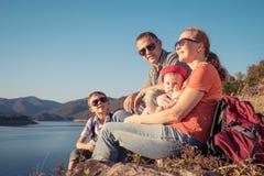 Ευτυχής οικογενειακή συνεδρίαση κοντά στη λίμνη στο χρόνο ημέρας Στοκ Εικόνες