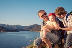 Ευτυχής οικογενειακή συνεδρίαση κοντά στη λίμνη στο χρόνο ημέρας Στοκ Φωτογραφία