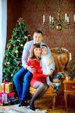Ευτυχής οικογενειακή συνεδρίαση σε μια καρέκλα κοντά σε ένα εορταστικό χριστουγεννιάτικο δέντρο στοκ φωτογραφία με δικαίωμα ελεύθερης χρήσης