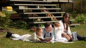 Ευτυχής οικογενειακή συνεδρίαση σε μια χλόη κατά τη διάρκεια του θερινού υπολοίπου στο χορτοτάπητα κίνηση αργή απόθεμα βίντεο