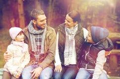 Ευτυχής οικογενειακή συνεδρίαση στον πάγκο και ομιλία στο στρατόπεδο Στοκ Φωτογραφία
