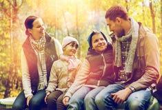 Ευτυχής οικογενειακή συνεδρίαση στον πάγκο και ομιλία στο στρατόπεδο Στοκ φωτογραφία με δικαίωμα ελεύθερης χρήσης