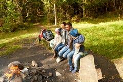 Ευτυχής οικογενειακή συνεδρίαση στον πάγκο στην πυρκαγιά στρατόπεδων Στοκ Εικόνα