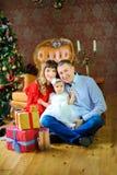 Ευτυχής οικογενειακή συνεδρίαση στο πάτωμα κοντά στα κιβώτια με τα δώρα και το χαμόγελο στοκ φωτογραφίες