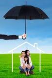 Ευτυχής οικογενειακή συνεδρίαση κάτω από το εικονίδιο και την ομπρέλα σπιτιών Στοκ Εικόνες