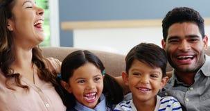 Ευτυχής οικογενειακή συνεδρίαση στον καναπέ και γέλιο στο καθιστικό απόθεμα βίντεο