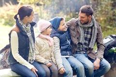 Ευτυχής οικογενειακή συνεδρίαση στον πάγκο και ομιλία στο στρατόπεδο Στοκ φωτογραφίες με δικαίωμα ελεύθερης χρήσης