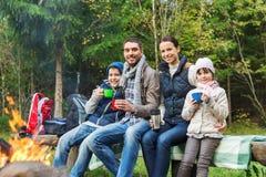 Ευτυχής οικογενειακή συνεδρίαση στον πάγκο στην πυρκαγιά στρατόπεδων Στοκ Εικόνες