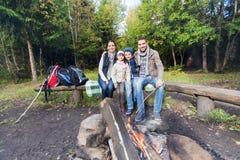 Ευτυχής οικογενειακή συνεδρίαση στον πάγκο στην πυρκαγιά στρατόπεδων Στοκ φωτογραφίες με δικαίωμα ελεύθερης χρήσης
