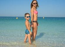 Ευτυχής οικογενειακή χαλάρωση θαλασσίως Ευτυχής οικογένεια που στηρίζεται στην παραλία το καλοκαίρι μητέρα με το αγοράκι που στηρ Στοκ Φωτογραφία