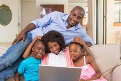 Ευτυχής οικογενειακή χαλάρωση στον καναπέ που χρησιμοποιεί το lap-top Στοκ Εικόνες