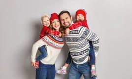 Ευτυχής οικογενειακοί μητέρα, πατέρας και παιδιά στα πλεκτά καπέλα και swe στοκ εικόνες