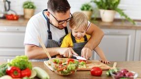 Ευτυχής οικογενειακός πατέρας με το γιο που προετοιμάζει τη φυτική σαλάτα Στοκ Εικόνες