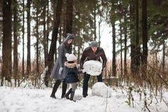 Ευτυχής οικογενειακός sculpts χιονάνθρωπος Στοκ φωτογραφία με δικαίωμα ελεύθερης χρήσης