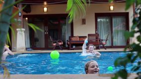 Ευτυχής ομάδα ελκυστικών νέων φίλων που παίζουν με τις σφαίρες που κολυμπούν σε μια πισίνα 1920x1080 φιλμ μικρού μήκους