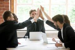 Ευτυχής ομάδα εργασίας που δίνει υψηλά πέντε μετά από να κλείσει την επιχειρησιακή διαπραγμάτευση στοκ φωτογραφία