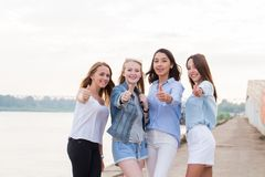 Ευτυχής ομάδα θηλυκών φίλων με την υπαίθρια εξέταση αντίχειρων επάνω τη κάμερα και το χαμόγελο στοκ εικόνες