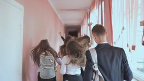 Ευτυχής ομάδα σπουδαστών γυμνασίου που τρέχουν κατά μήκος του διαδρόμου απόθεμα βίντεο