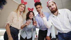 Ευτυχής ομάδα στα καπέλα santa που κάνουν τη τηλεσύσκεψη και που τα γυαλιά με το λαμπιρίζοντας κρασί στο εταιρικό κόμμα γραφείων  απόθεμα βίντεο
