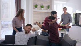 Ευτυχής ομάδα φίλων που παίζουν τα παιχνίδια στον υπολογιστή στον καναπέ και που έχουν τη διασκέδαση στο σύγχρονο διαμέρισμα απόθεμα βίντεο