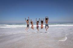 Ευτυχής ομάδα φίλων που πηδούν μαζί στην παραλία στην ηλιοφάνεια στοκ εικόνα