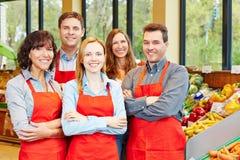Ευτυχής ομάδα προσωπικού στην υπεραγορά στοκ εικόνες