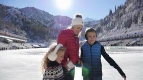 Ευτυχής πάγος παιδιών και μητέρων που κάνει πατινάζ στην αίθουσα παγοδρομίας υπαίθρια στο χειμώνα απόθεμα βίντεο