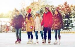 Ευτυχής πάγος φίλων που κάνει πατινάζ στην αίθουσα παγοδρομίας υπαίθρια Στοκ Εικόνες