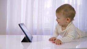 Ευτυχής παιδική ηλικία, σύγχρονα κινούμενα σχέδια προσοχής μικρών παιδιών στην ταμπλέτα στο φωτεινό δωμάτιο απόθεμα βίντεο