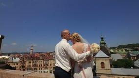 Ευτυχής πανέμορφη νύφη και μοντέρνος νεόνυμφος με τις αληθινές συγκινήσεις στη στέγη στο υπόβαθρο της άποψης των παλαιών κτηρίων  φιλμ μικρού μήκους
