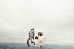 Ευτυχής πανέμορφη νύφη και μοντέρνος νεόνυμφος που πηδούν και που έχουν τη διασκέδαση, β Στοκ Φωτογραφία