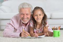 Ευτυχής παππούς με την εγγονή που σύρει από κοινού Στοκ Εικόνα