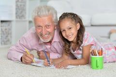 Ευτυχής παππούς με την εγγονή που σύρει από κοινού Στοκ φωτογραφίες με δικαίωμα ελεύθερης χρήσης