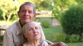 Ευτυχής παππούς που αγκαλιάζει τη σύζυγό του στο πάρκο φιλμ μικρού μήκους