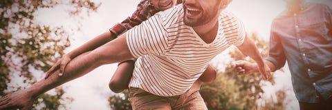 Ευτυχής παππούς που εξετάζει το άτομο που δίνει piggybacking στο γιο στοκ εικόνες